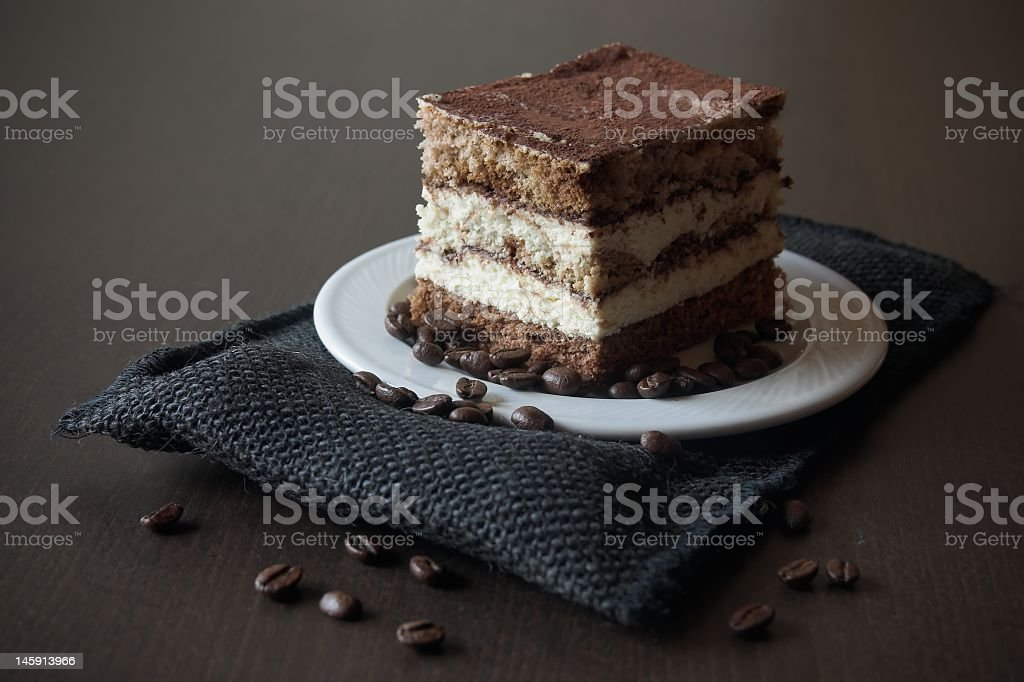 Slice of tiramisu with coffee beans on a dark table royalty-free stock photo