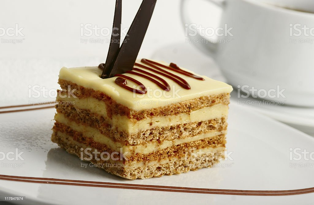Slice of  vanilla cream cake with chocolate decoration closeup stock photo