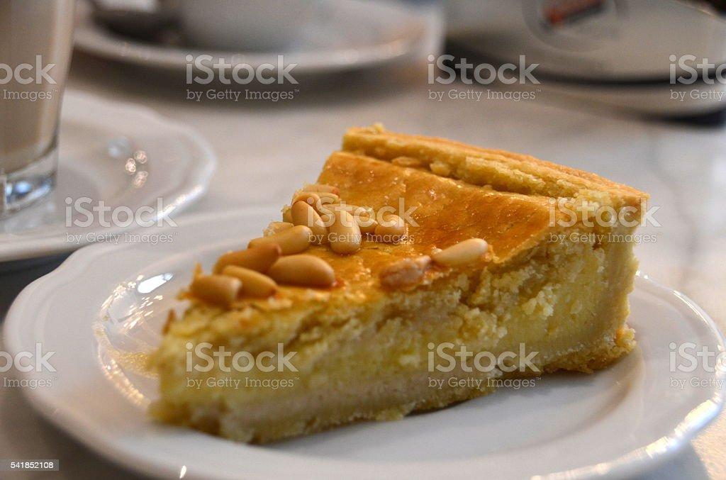 Slice of vanilla custard tart with pine nuts on top stock photo