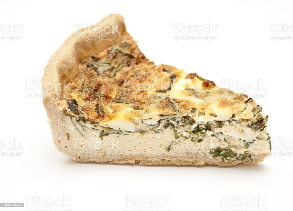 slice of vegetable quiche against white stock photo