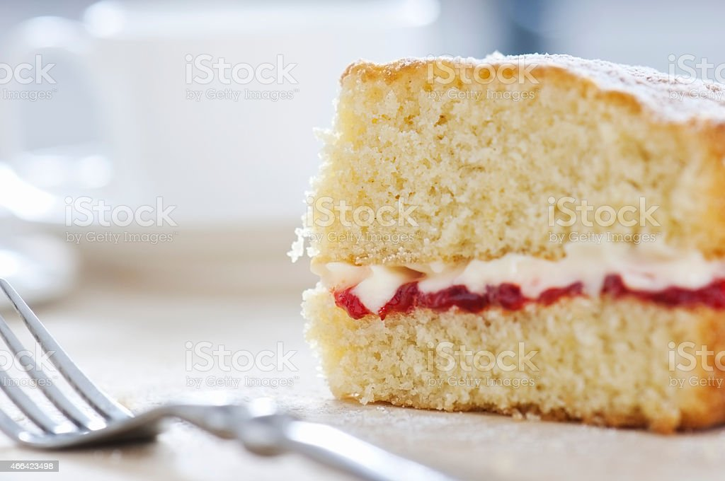 Slice of Victoria sponge cake dusted with icing sugar stock photo