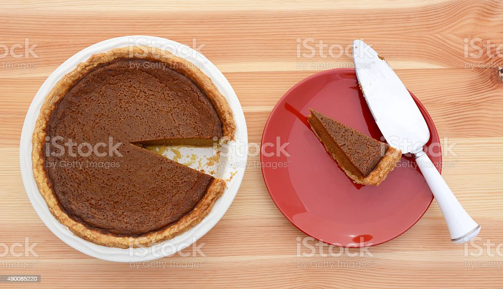 Slice taken from a pumpkin pie with pie server stock photo