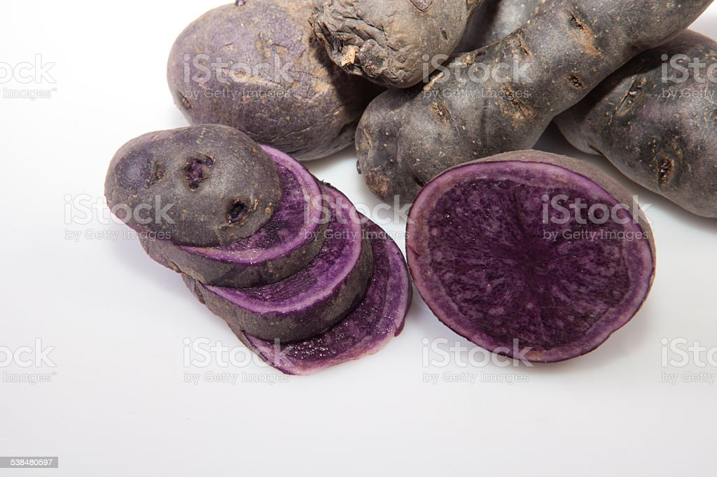 Sliced and whole Vitelotte potatoes stock photo