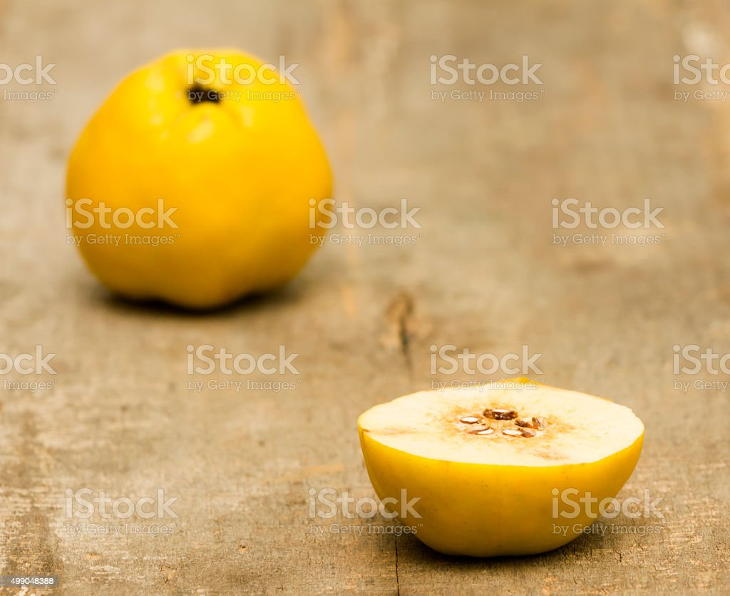 Sliced apple quince on old wooden plank stock photo