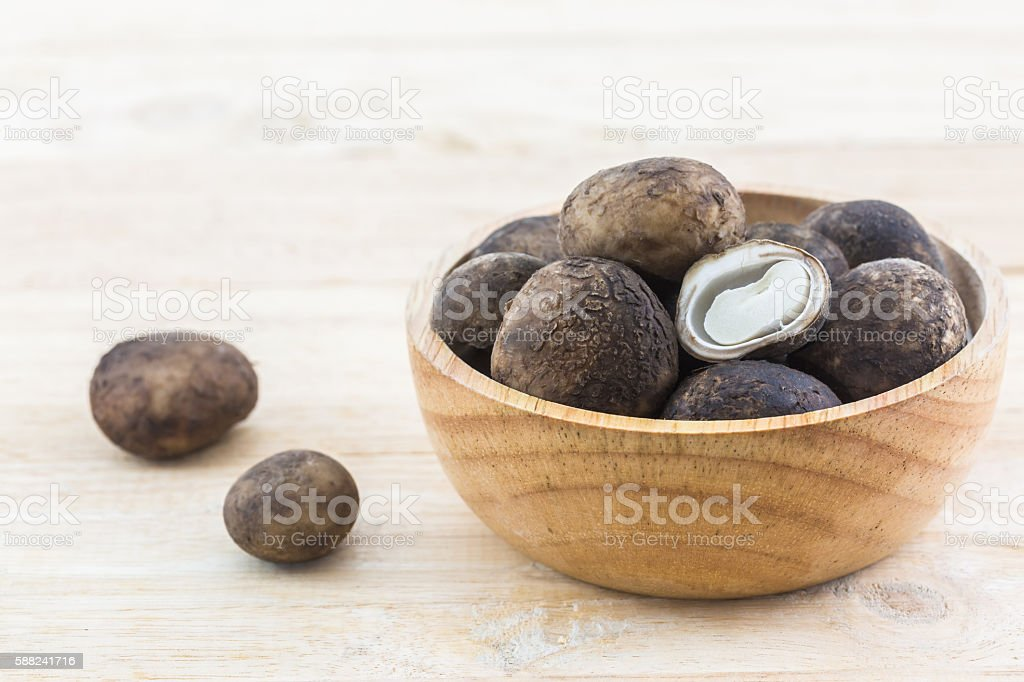 Sliced Barometer Earthstars mushroom in the wood bowl on wood background. stock photo