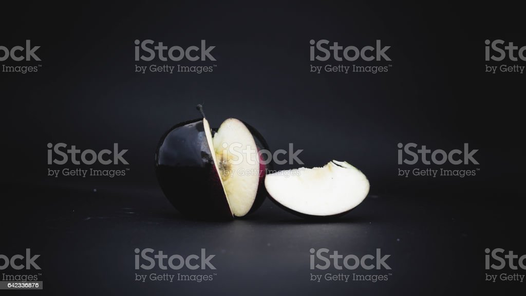 sliced black apple on a background stock photo