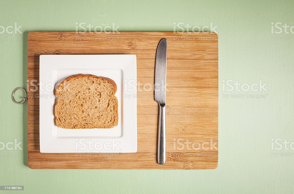Sliced brown bread on square white plate with knife royalty-free stock photo