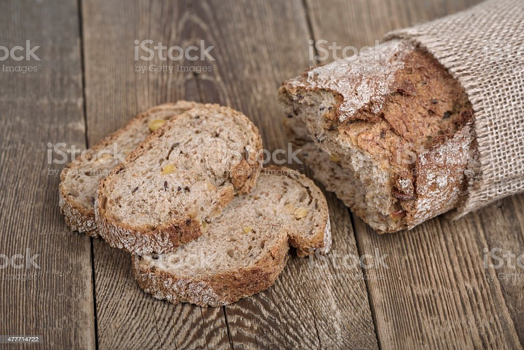 Sliced brown bread on wooden table. stock photo