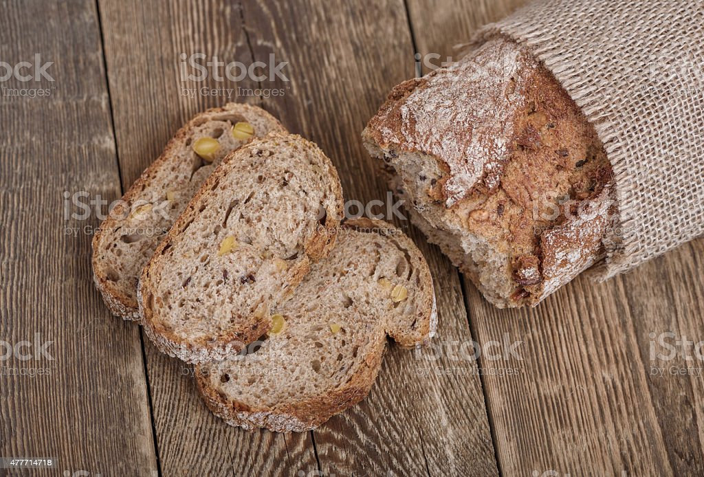 Sliced brown bread on wooden table. Top view. stock photo