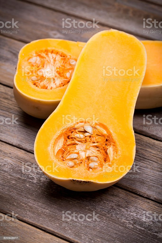 Sliced butternut squash over old wood stock photo