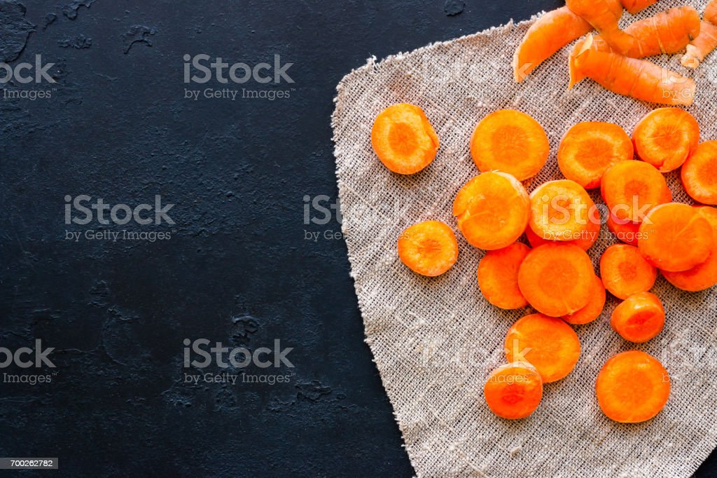Sliced carrots on a napkin and place for text on a black background stock photo