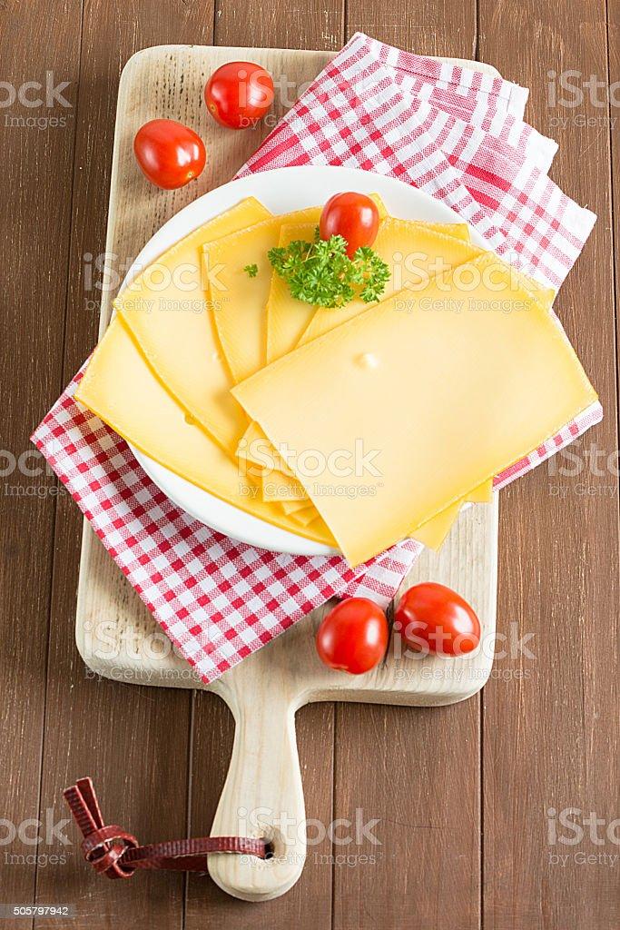 In Scheiben geschnittener Käse liegt auf einem Holzbrett stock photo