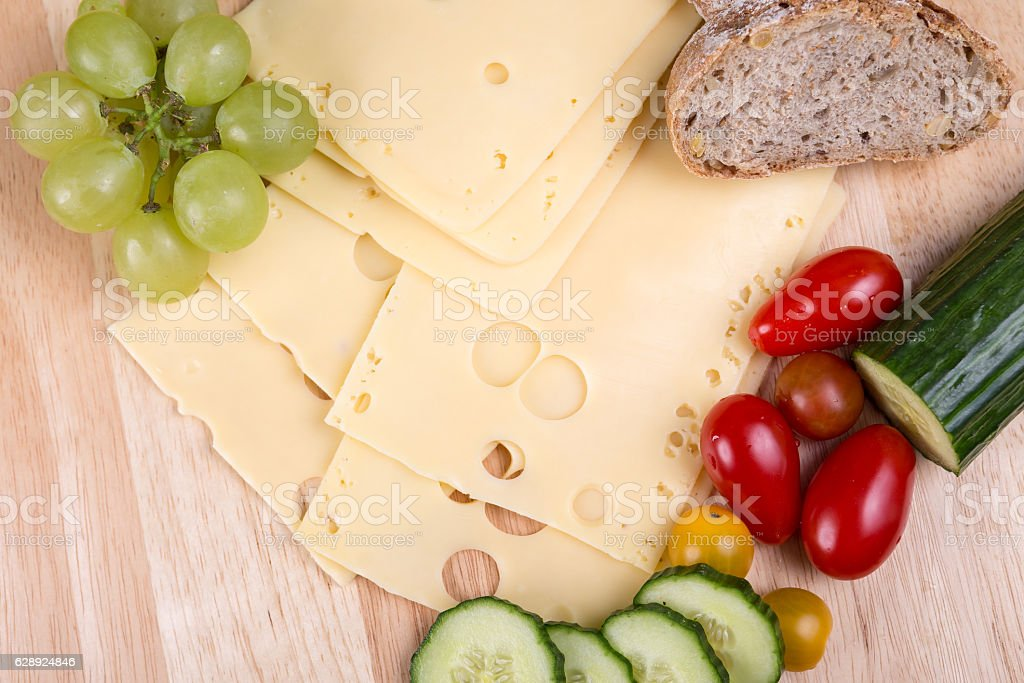 Sliced cheese on a cutting board stock photo
