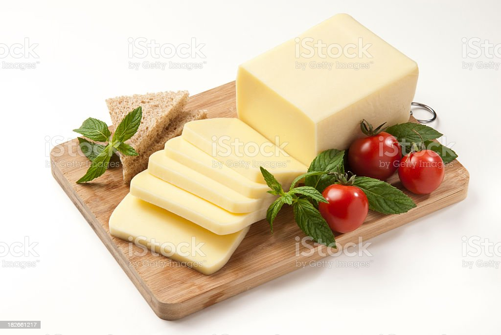 Sliced cheese, tomatoes and herbs in a cutting board stock photo