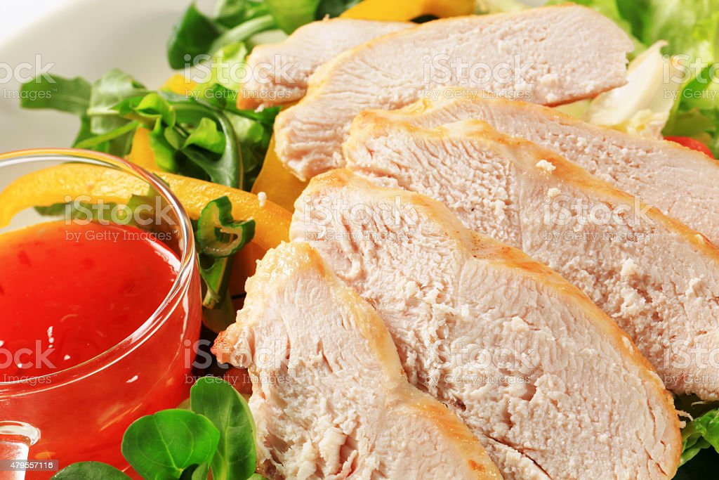 Sliced chicken breast with salad and sweet chilli sauce stock photo