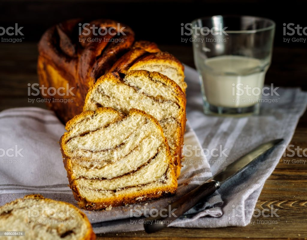 Sliced cinnamon bread with glass of milk on the wooden table. stock photo