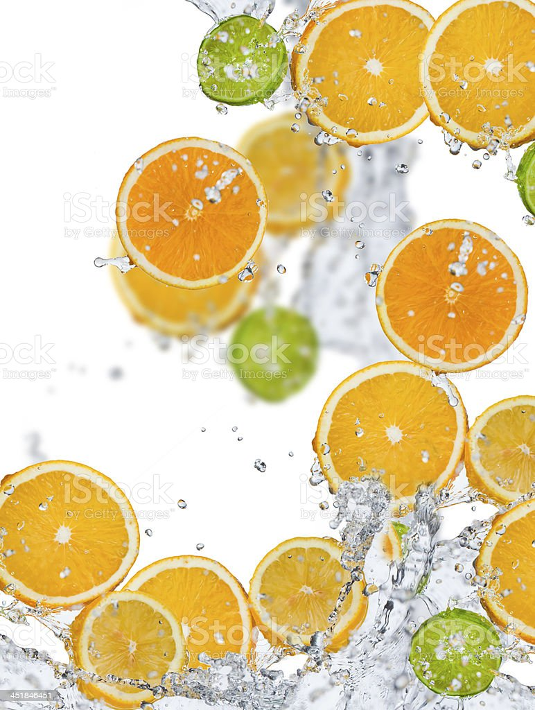 Sliced citrus fruits and splashing water on white stock photo