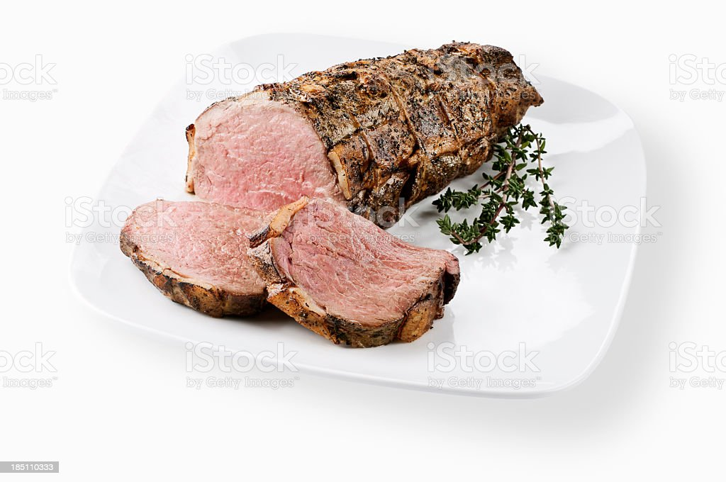 A sliced cooked tenderloin of beef on a white platter stock photo