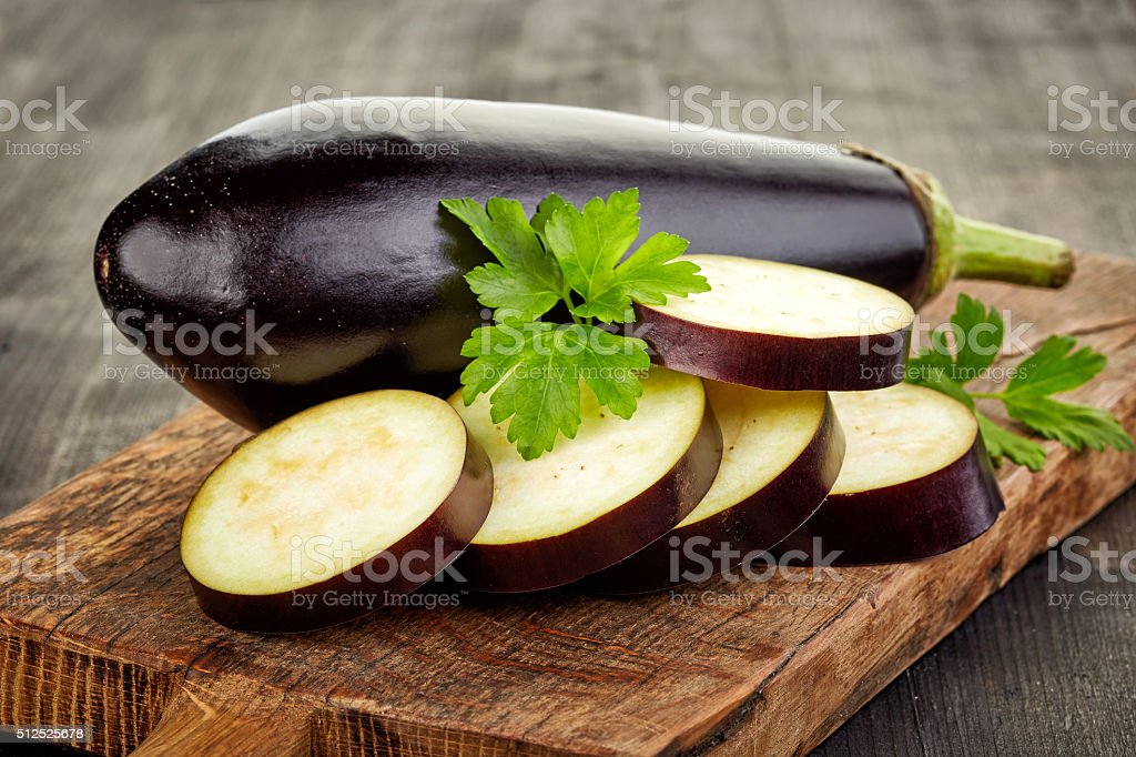 sliced eggplant on cutting board stock photo