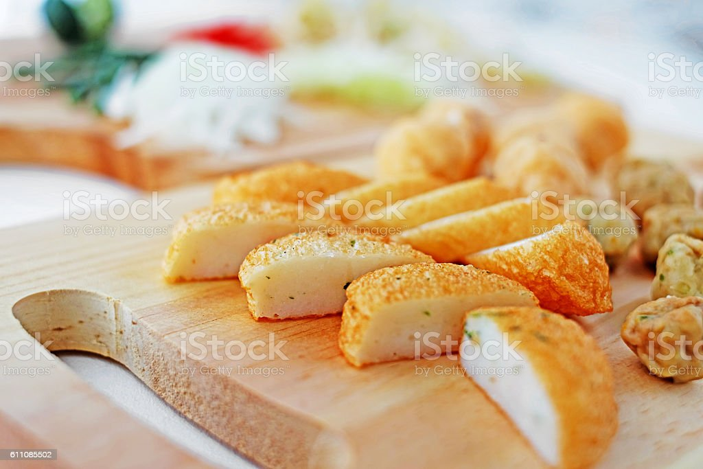 Sliced fish cake laksa on wooden cutting board in kitchen stock photo