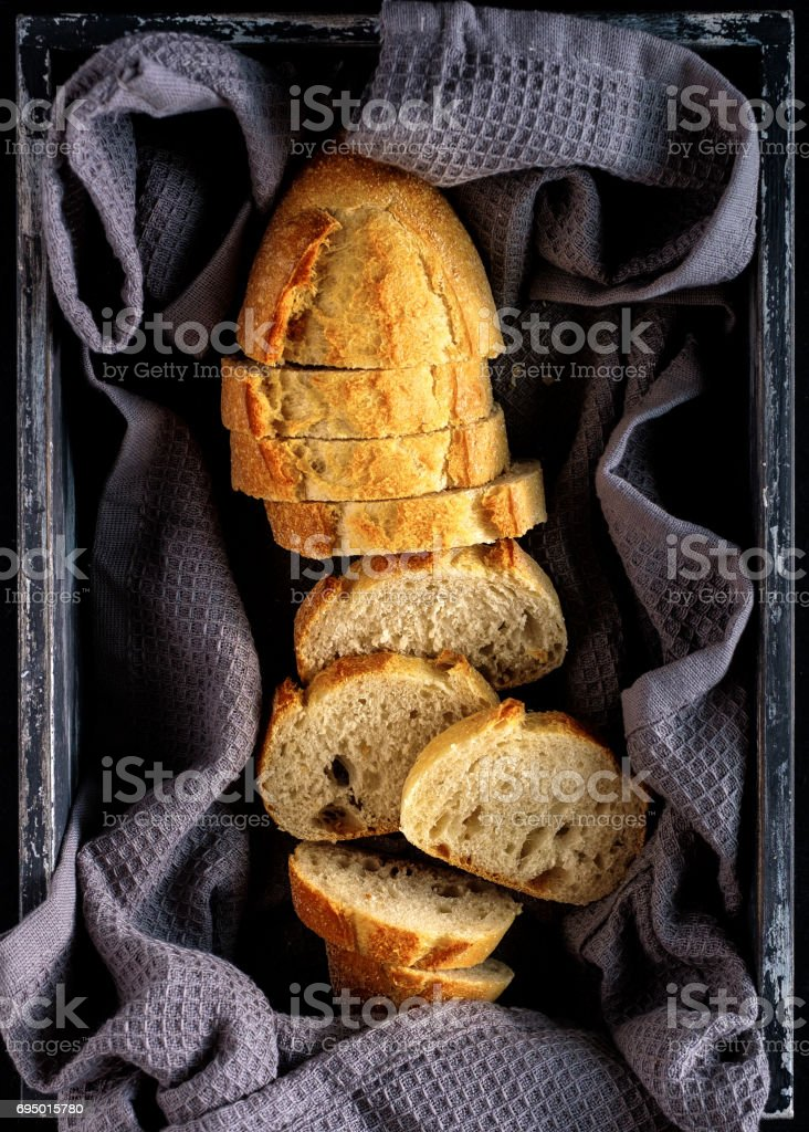 Sliced fresh bread in wooden box. Top view stock photo