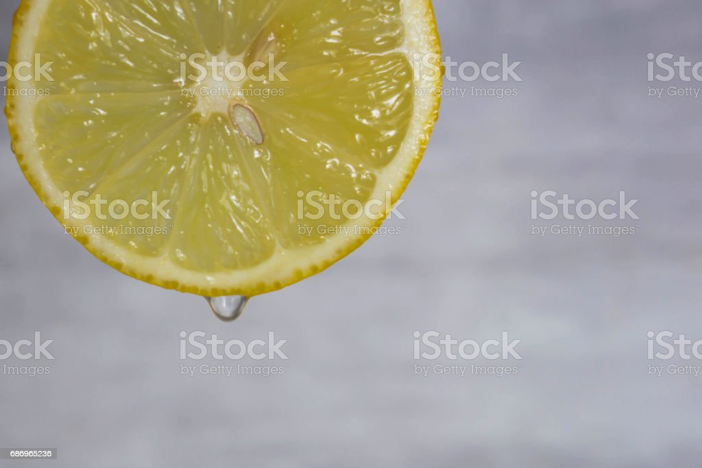 Sliced fresh lemon with a falling drop of juice stock photo