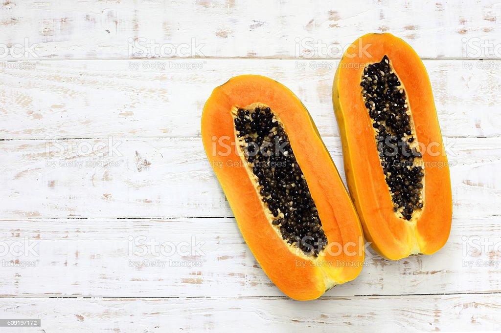 Sliced fresh papaya on white wooden background stock photo