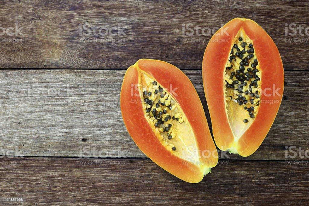 Sliced fresh papaya on wooden background stock photo