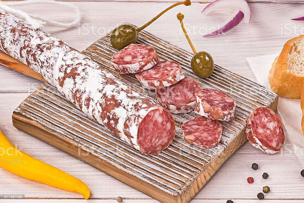 Sliced Fuet Salami on rustic cutting board stock photo