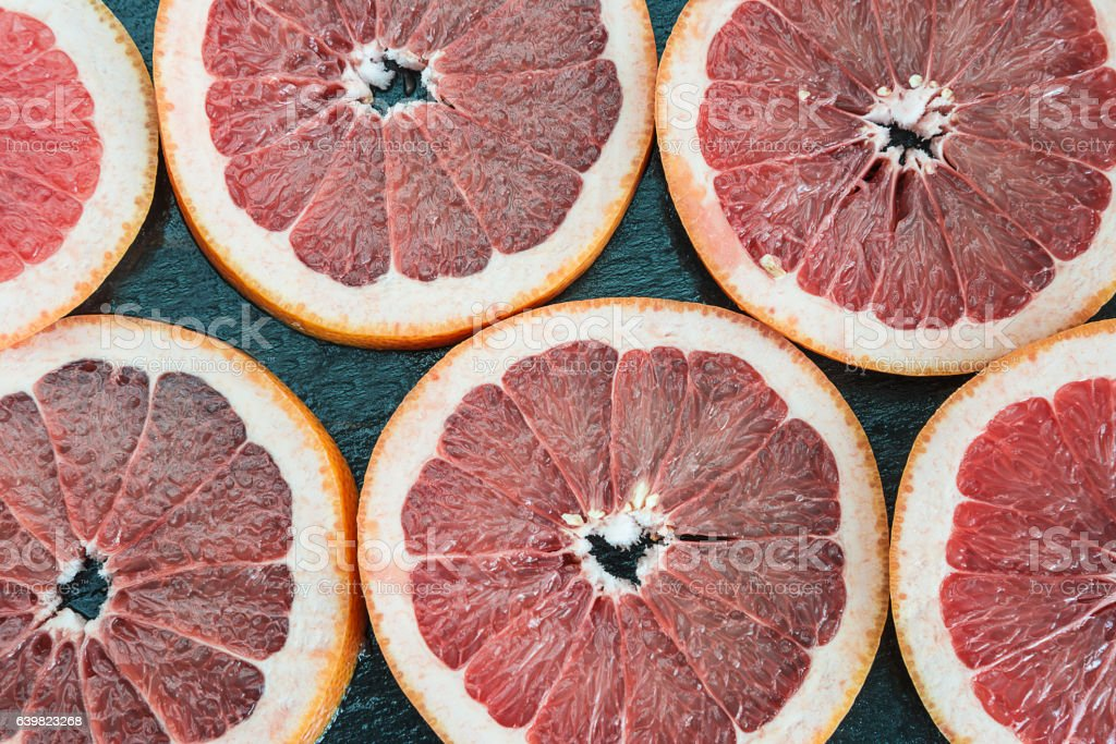sliced grapefruit on black slate background stock photo