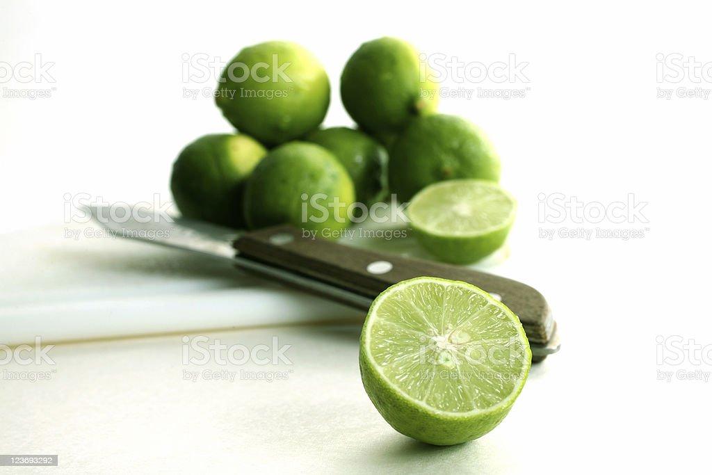 Sliced green limes. Knife. White background. Fresh fruit. stock photo