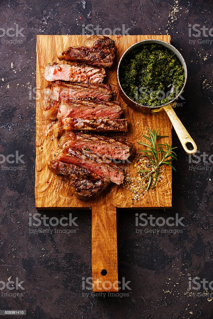 Sliced grilled beef Sirloin steak with chimichurri sauce stock photo