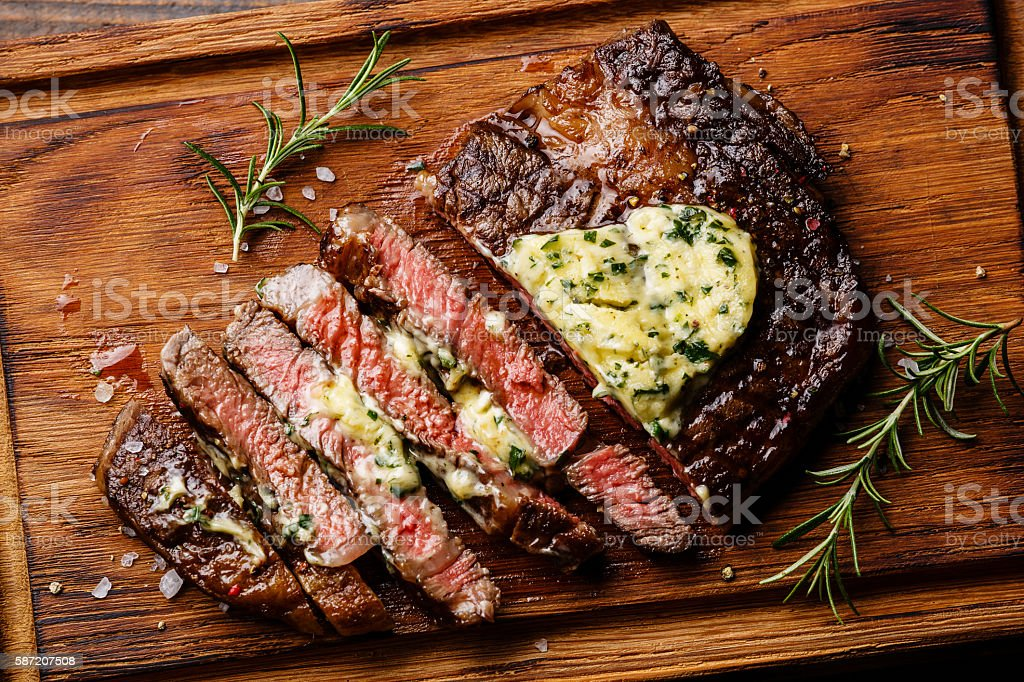 Sliced grilled steak Ribeye with herb butter stock photo