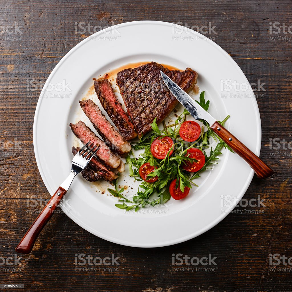 Sliced grilled steak Striploin and salad with tomatoes and arugula stock photo