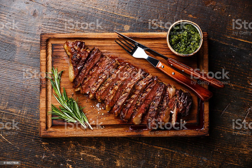 Sliced grilled Striploin steak with chimichurri sauce stock photo