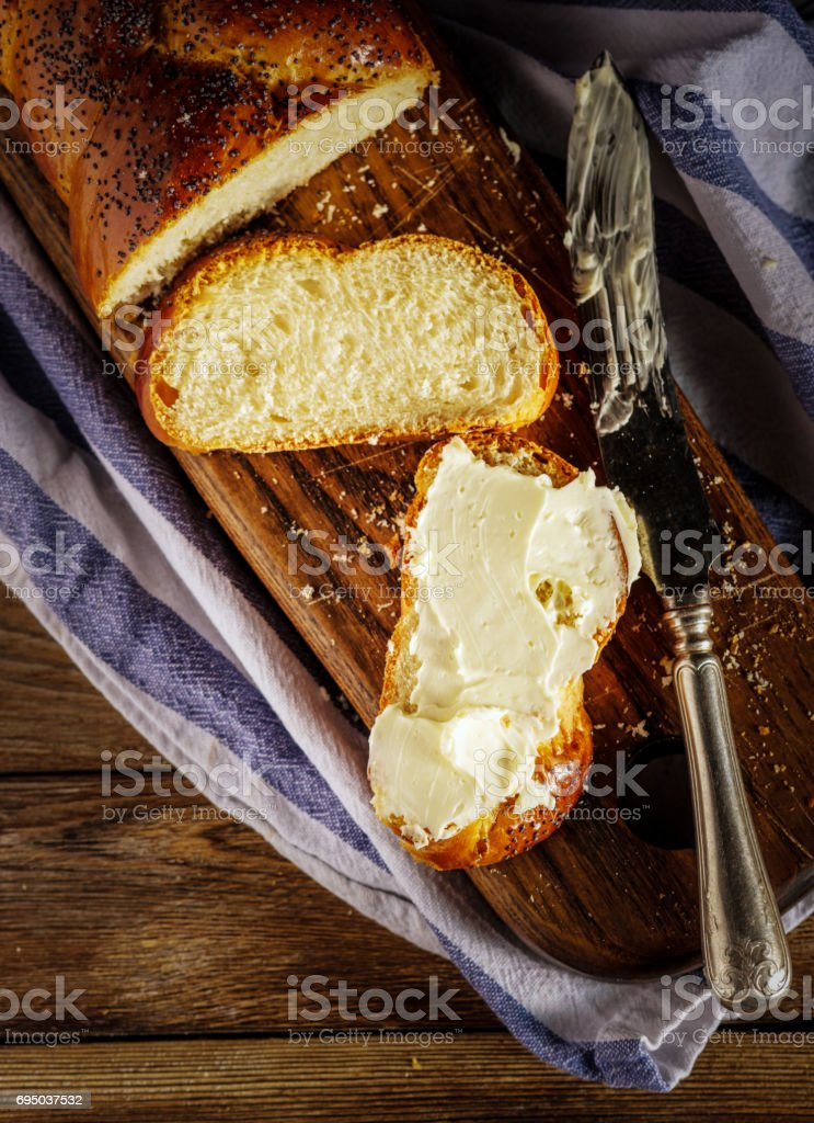 Sliced Hala with butter is a traditional jewish sweet fresh sabbath bread loaf. stock photo