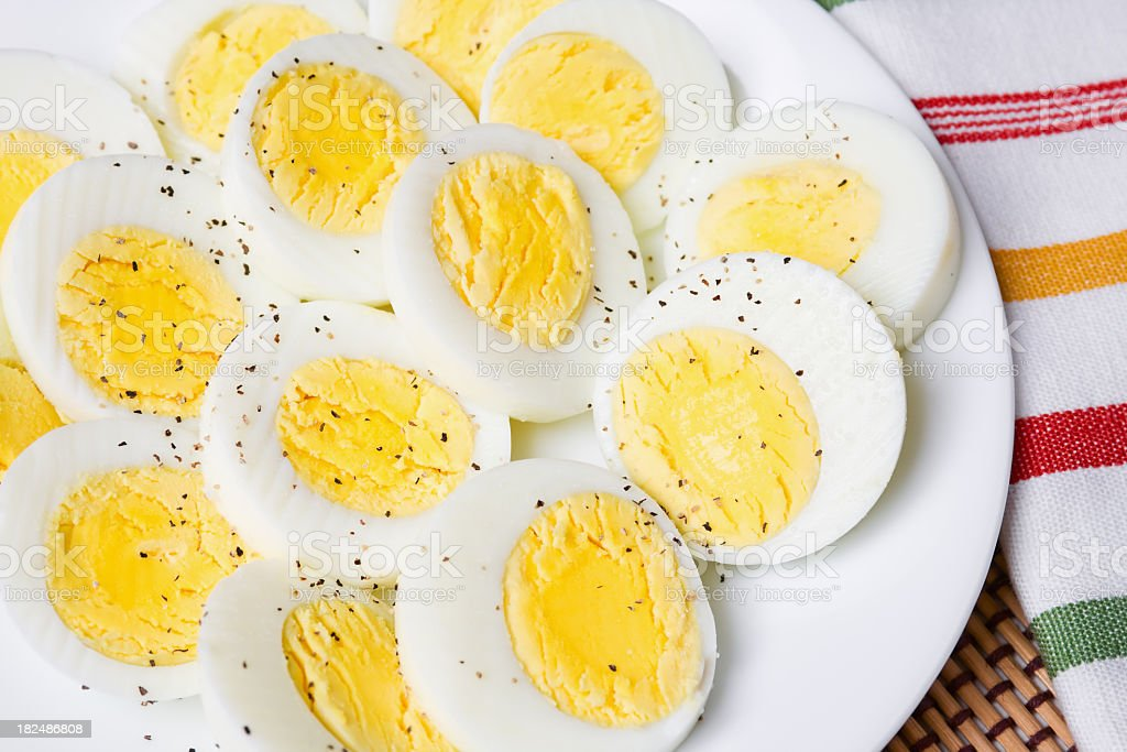Sliced hard boiled eggs with salt and pepper royalty-free stock photo