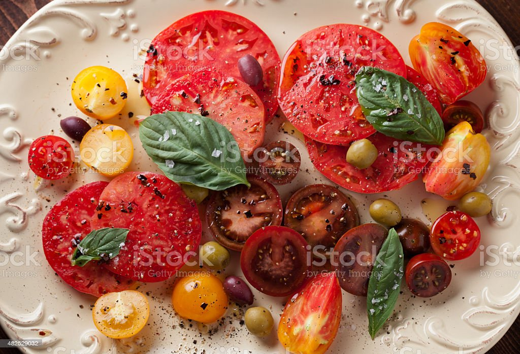 Sliced Heirloom Tomatoes And Olives On A Plate stock photo