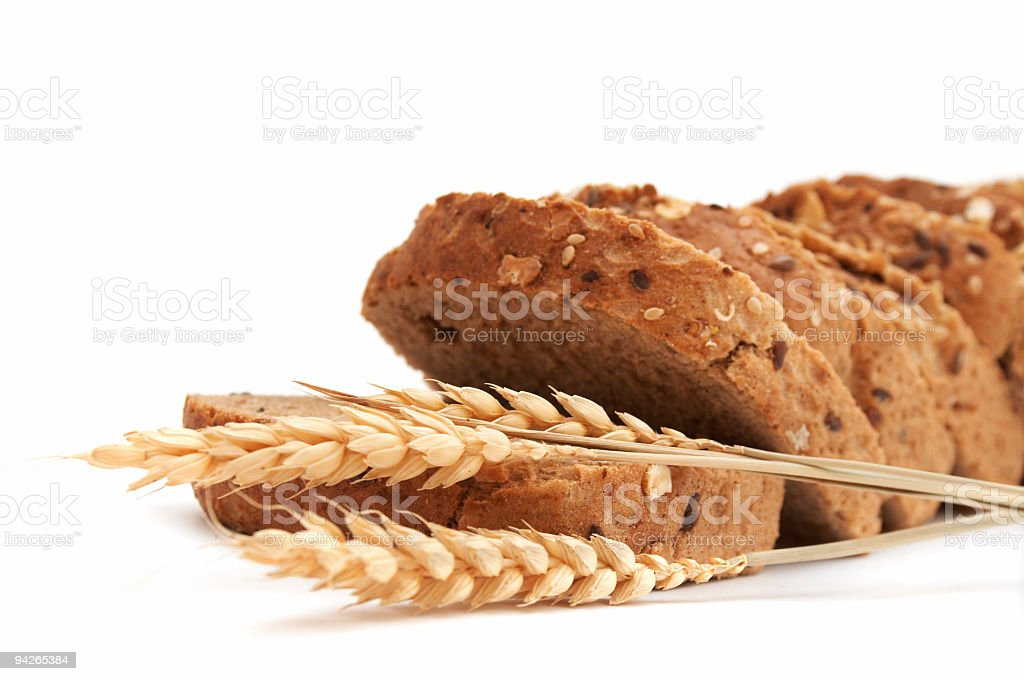 Sliced integral bread of seeds and two ears of wheat royalty-free stock photo