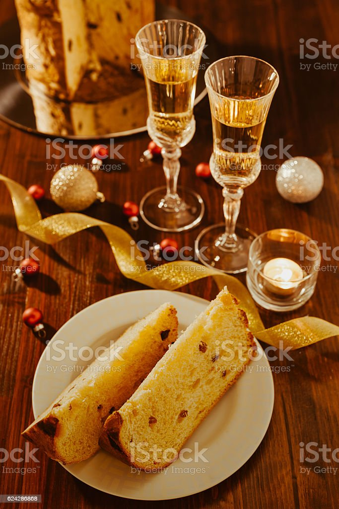 Sliced italian panettone, sparkling wine and decorations over a table stock photo