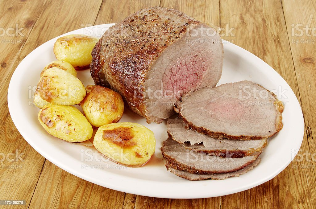 Sliced Joint Of Roast Beef And Potatoes on Plate stock photo