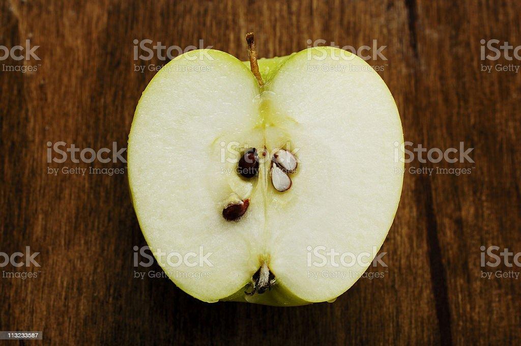 sliced juicy crisp fresh green apple from above, against oak royalty-free stock photo