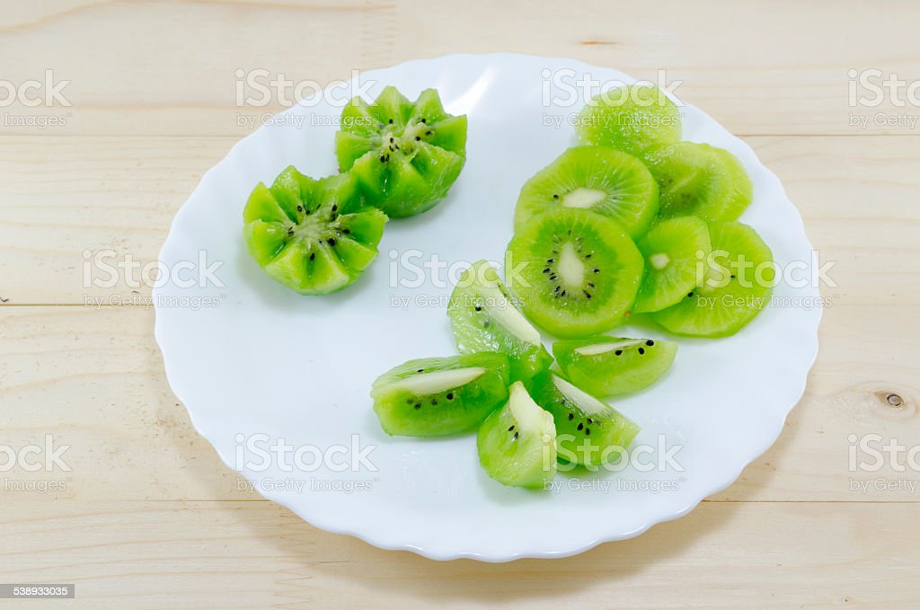 Sliced kiwi placed on a white plate royalty-free stock photo