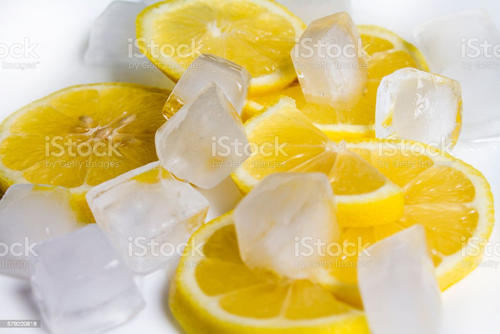 sliced lemon fruits and lots of ice cubes stock photo