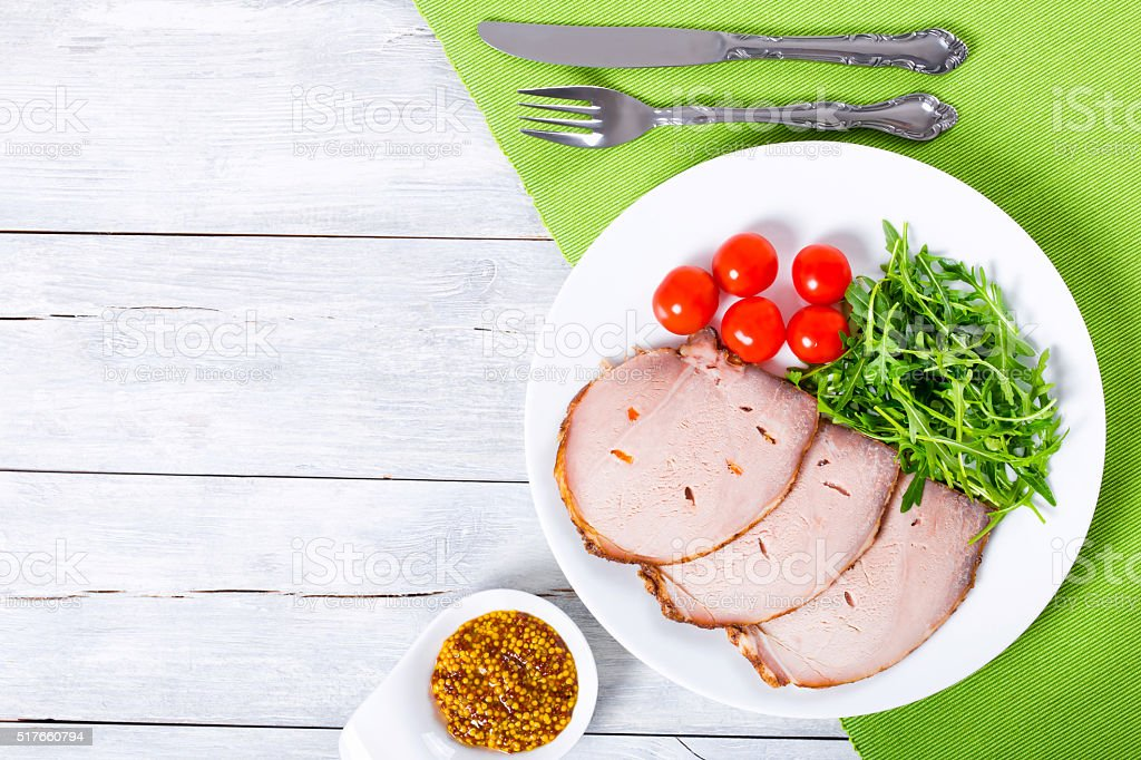 Sliced meat with arugula salad, cherry tomatoes, top view, close-up stock photo