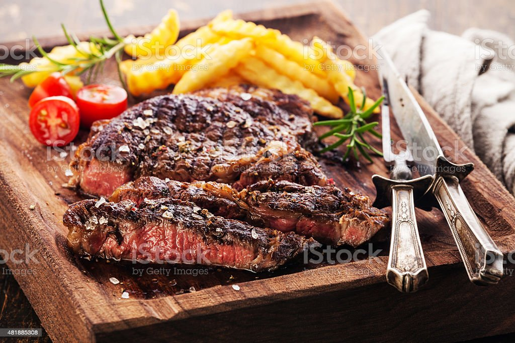 Sliced medium rare grilled Steak Ribeye with french fries stock photo