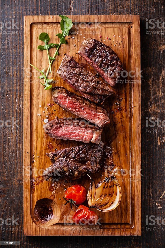 Sliced medium rare grilled steak Ribeye with grilled onions stock photo
