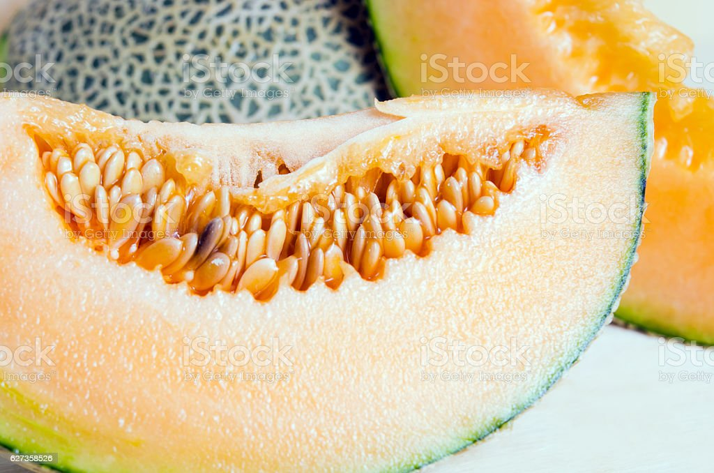 Sliced melon with seed on wooden board stock photo
