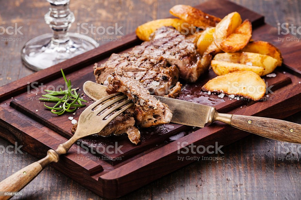 Sliced New York steak with potato wedges stock photo