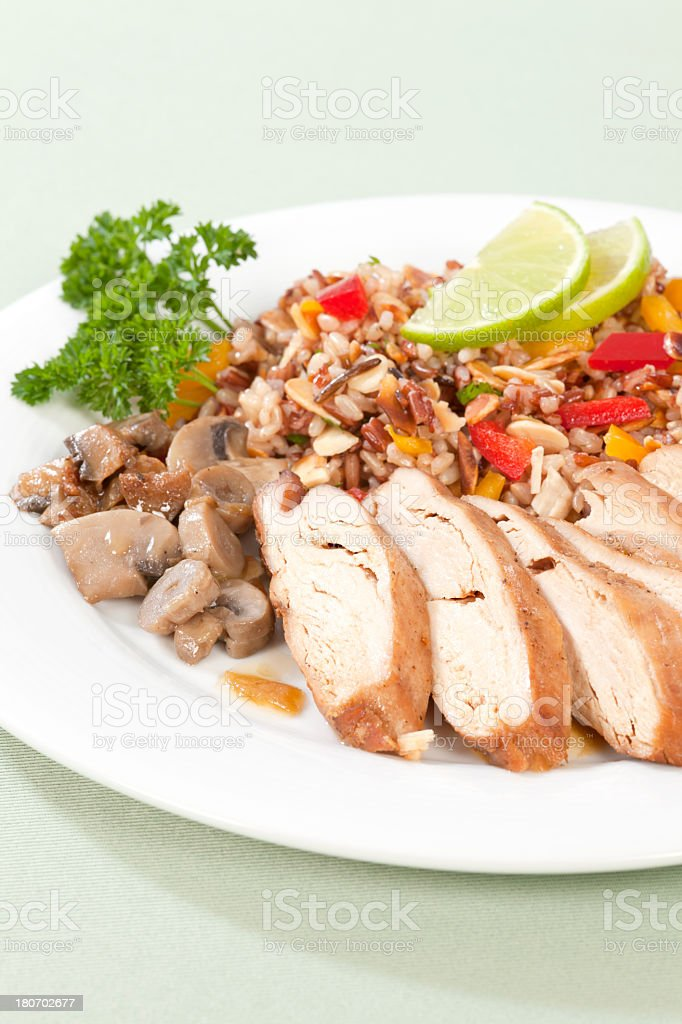 Sliced of chicken with colored rice stock photo